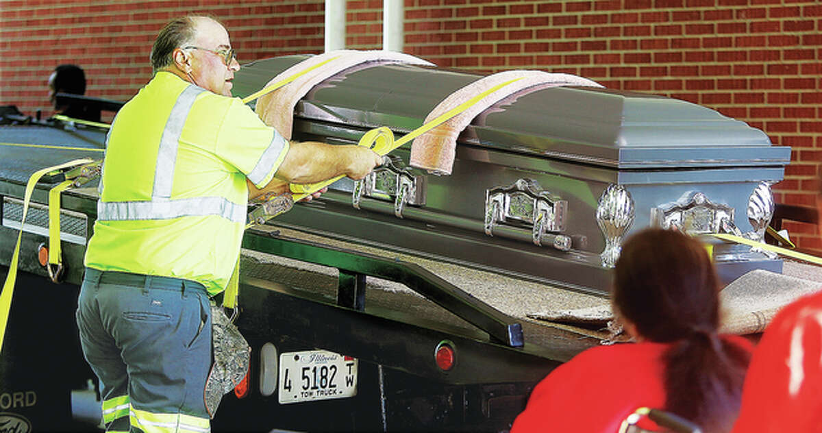 Tow truck operators helped load Klaffer's coffin onto the flatbed truck and strap it down for the ride from Alton to Grafton.