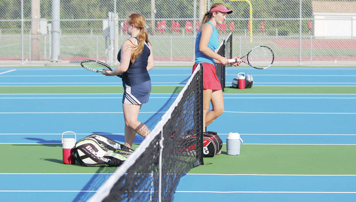 Players change sides during a girls tennis match between Roxana and Althoff Catholic High School Tuesday. The match was the first played on Roxana's new tennis courts this season.
