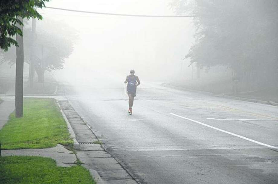 A lone runner makes his way through the dense fog Saturday in west Jacksonville before the start of the Passavant-Powerade 5K/10K. Photo: David Blanchette | Journal-Courier