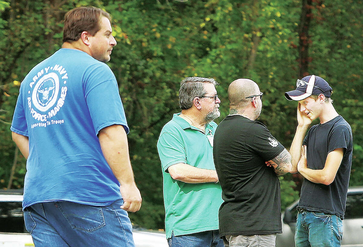 """Employees of Hanley Industries, 3640 Seminary Road, huddle around after what was described as """"multiple explosions"""" occurred at the plant Thursday. The employee on the right appears to be giving an intense account as Fosterburg firefighters arrive on scene. Gates at the plant, which is known to make specialty explosives, were closed and visitors were turned away. Neighbors reported hearing the explosions over the operation of a leaf blower, but no injuries were reported."""