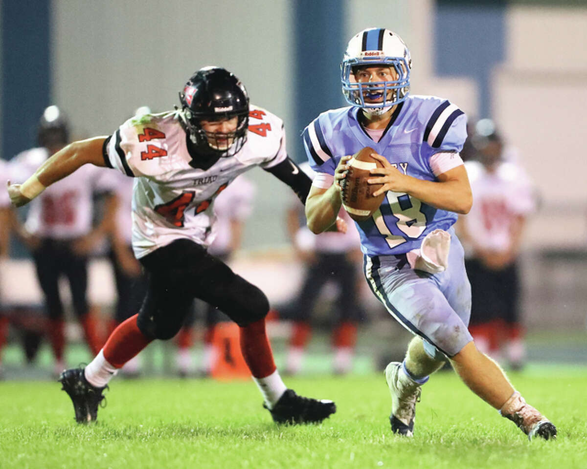 Jersey quarterback Drew Sauerwein (right) is chased out of the pocket by Triad's Colin Brunton during a Mississippi Valley Conference game Sept. 23 at Snyders Sports Complex in Jerseyville. Jersey lost the game 48-21 and looks to end its five-game losing streak Friday night at Mascoutah.