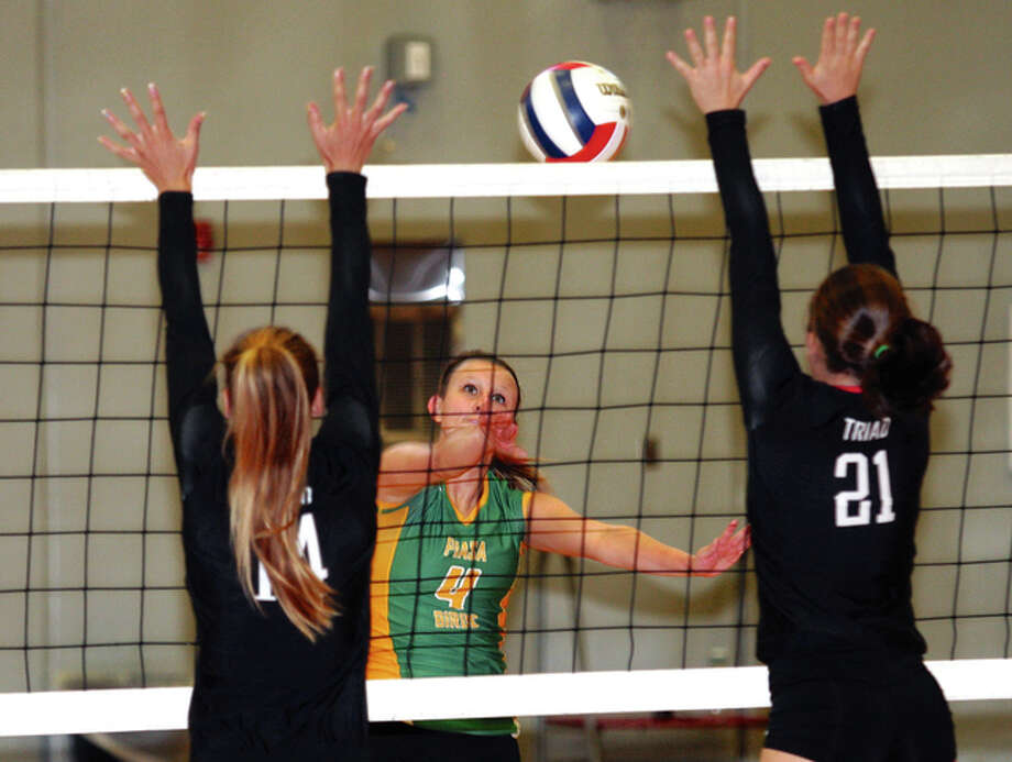 Southwestern's Jenna Moore (middle), shown in a match last season sending the ball through the block put up by Triad's Abby Richter (left) and Hannah Johnson, and the Piasa Birds fell to the Gillespie Miners in a South Central Conference match Thursday in Piasa. Photo: James B. Ritter / For The Telegraph