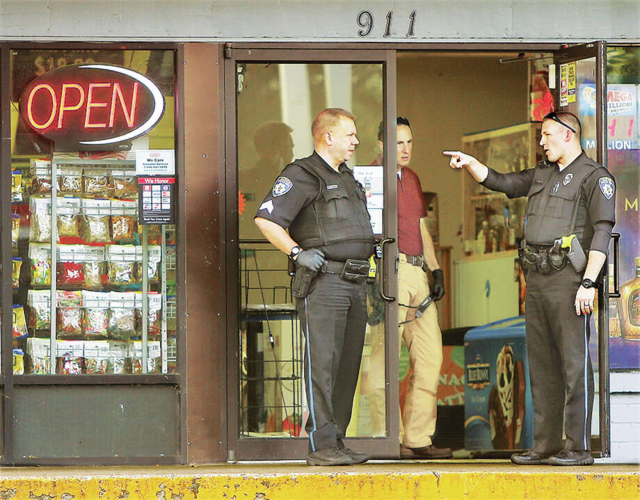 Alton Police officers and detectives talk in the doorway of the Conoco station at 911 College Avenue on State House Square, also known locally as the circle, Friday morning following a robbery of the establishment.
