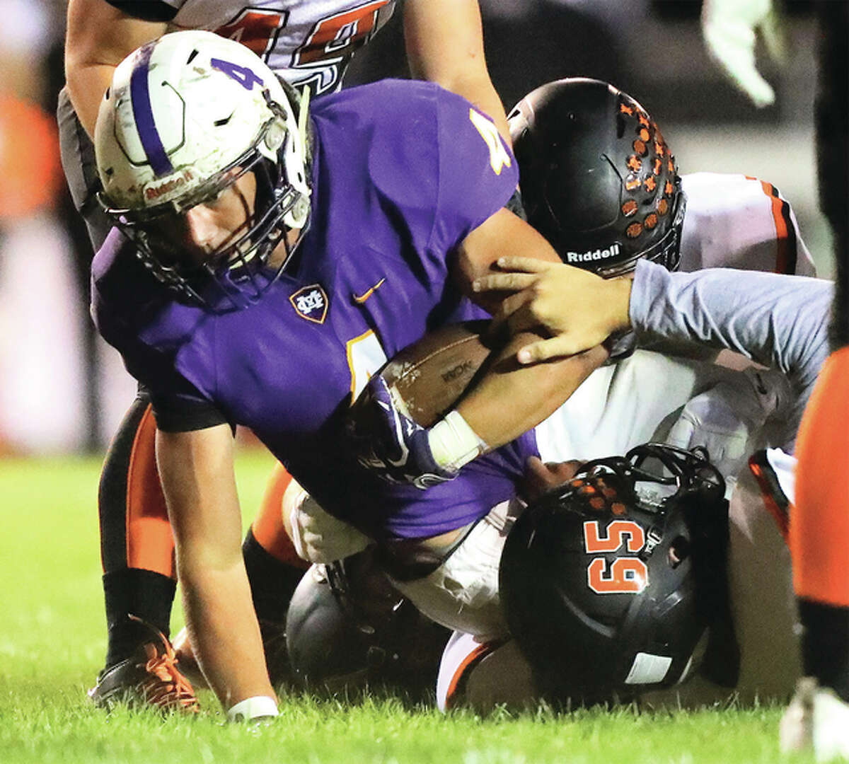 Civic Memorial's Nick Newell fights for extra yards as he is tackled by a host of Waterloo defenders during Friday night's Mississippi Valley Conference game in Bethalto. CM won 20-15 to improve to 5-2.