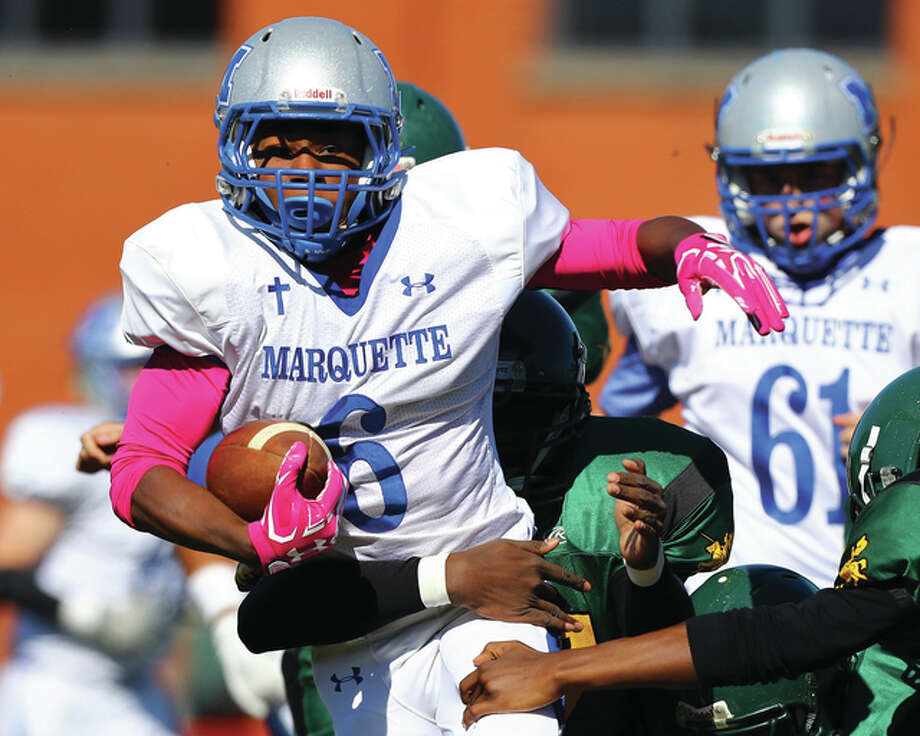 Marquette Catholic's Treven Swingler (left) runs the ball against the Metro East Lutheran Knights during Saturday afternoon's Prairie State Conference football game in Madison. Marquette won 48-0 to improve its record to 5-2 and 5-0 in the PSC while extending its winning streak to five in a row. MEL, in the final year of its co-op agreement with Madison, is 0-7. The Explorers got three rushing touchdowns from D'Avion Peebles, who also threw a TD pass. Photo: Billy Hurst / For The Telegraph