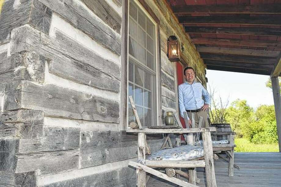 Bryan Leonard stands on the front porch of his recently completed log cabin south of Jacksonville. Leonard and his wife, Heather, are renting out the cabin through Airbnb, an online network of places to stay.