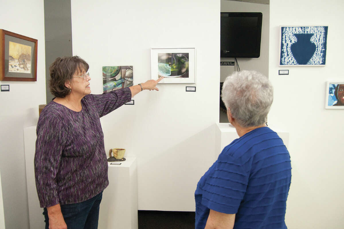 Wood River History Museum Art Show co-chairwoman Cheryl Maguire gives information to Janet Hunt about a photograph by Patrick Bellman. Bellman was one of 55 entrants with artwork at the fourth annual Wood River Museum Art Show Sunday.