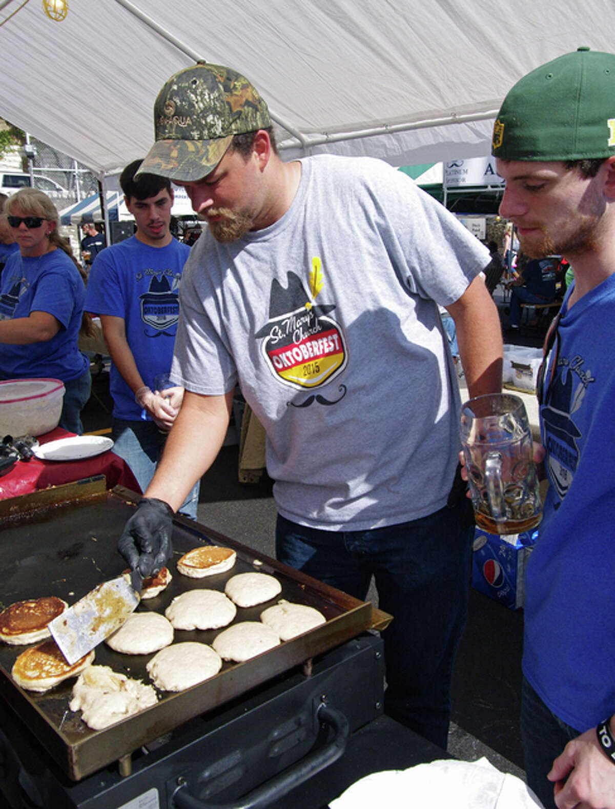 Nathan Taul, of Alton, left, and Mike Grossheim, of Godfrey, prepare potato pancakes during the St. Mary's Oktoberfest in Alton Sunday.