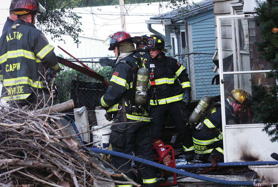 Alton and East Alton firefighters process the scene of a suspicious fire Sunday evening at 2814 E. Broadway.
