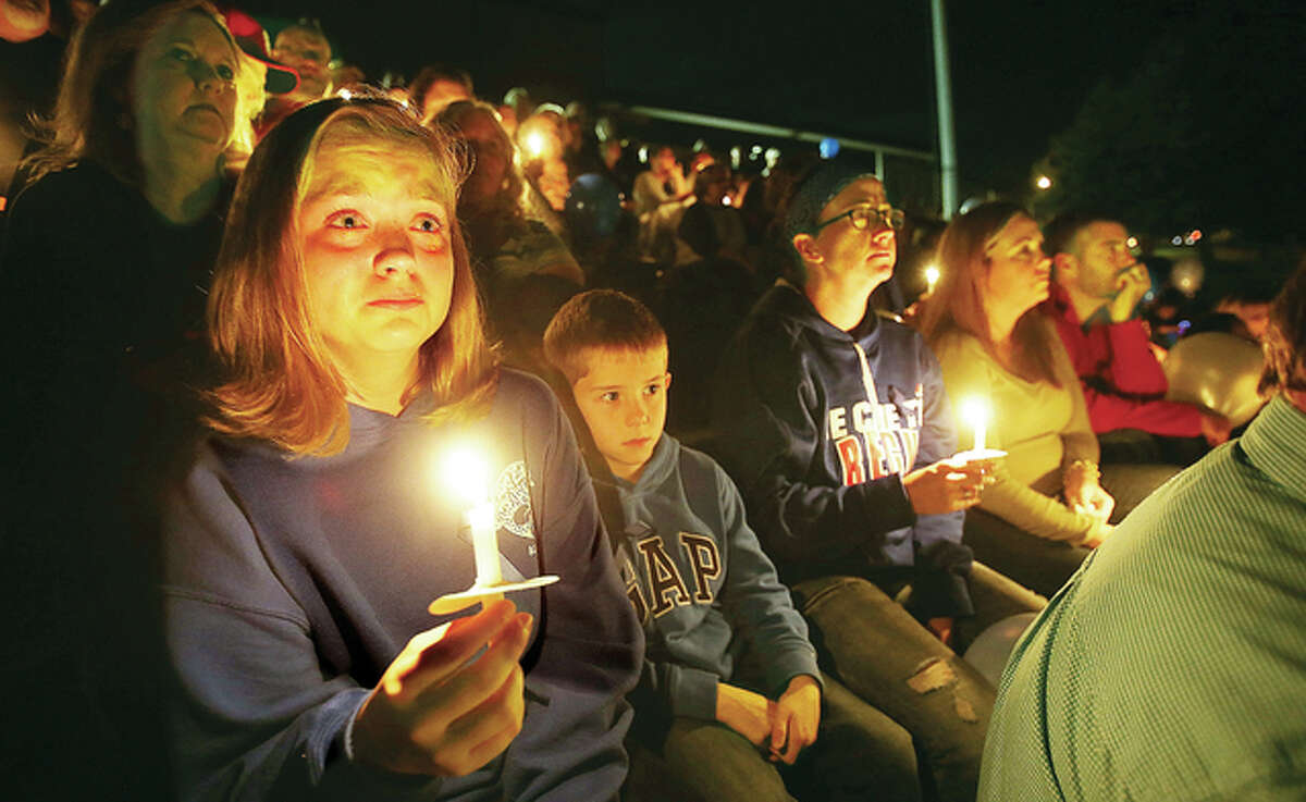 """A young woman cries as she holds a candle with hundreds of others who gathered in Alton's Public School Stadium Monday evening to honor St. Louis County Police officer Blake Snyder, originally from Godfrey, who was shot and killed in an exchange of gunfire on Thursday, Oct. 6. The Alton Police Honor Guard placed a wreath, the crowd listened to """"Amazing Grace"""" and the national anthem, and several close friends of Snyder's spoke of their memories of the former high school soccer player."""