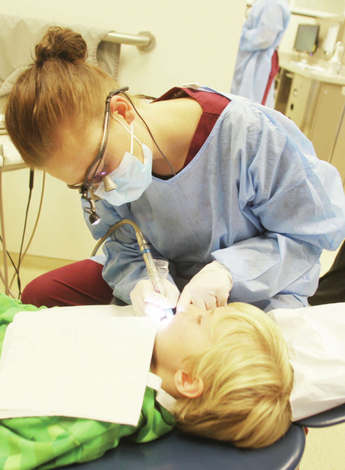 Lewis and Clark Community College dental hygiene student Samantha Swigonski, of Edwardsville, cleans Ty Inman's teeth Monday at the annual Give Kids a Smile Day at Southern Illinois University School of Dental Medicine in Alton. More than 400 volunteers help to provide free dental care to approximately 300 children from around the Metro East.