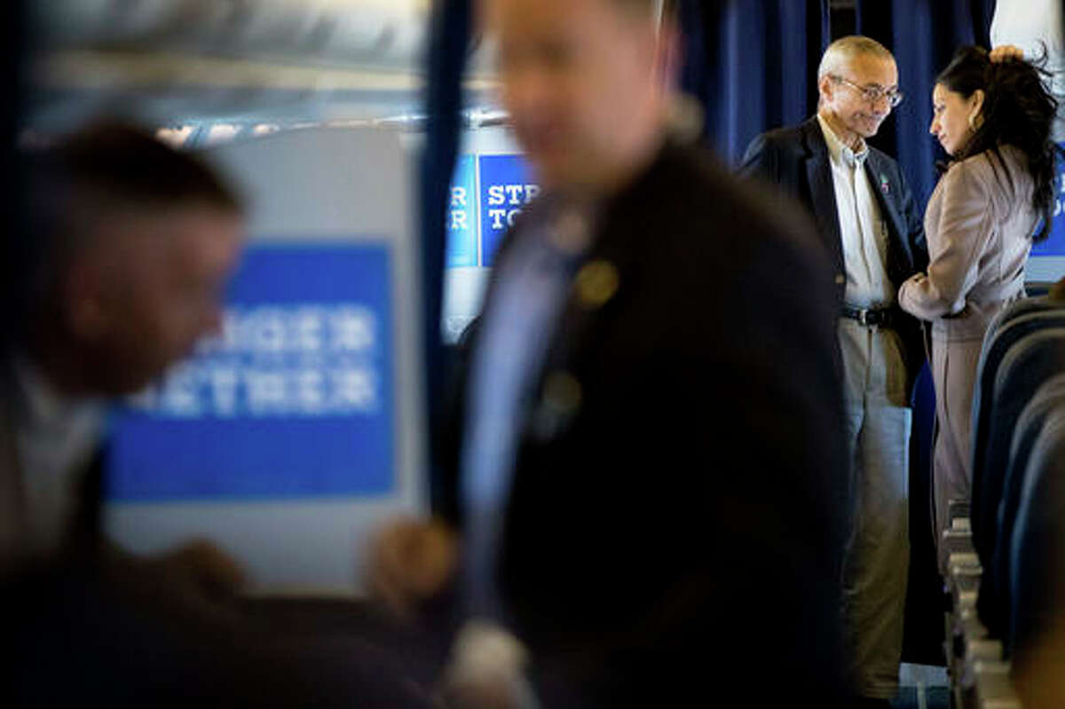 Hillary Clinton's campaign manager John Podesta, second from right, pauses while speaking with senior aide Huma Abedin aboard Clinton's campaign plane while traveling to Miami, Tuesday, Oct. 11, 2016, for a rally. (AP Photo/Andrew Harnik)