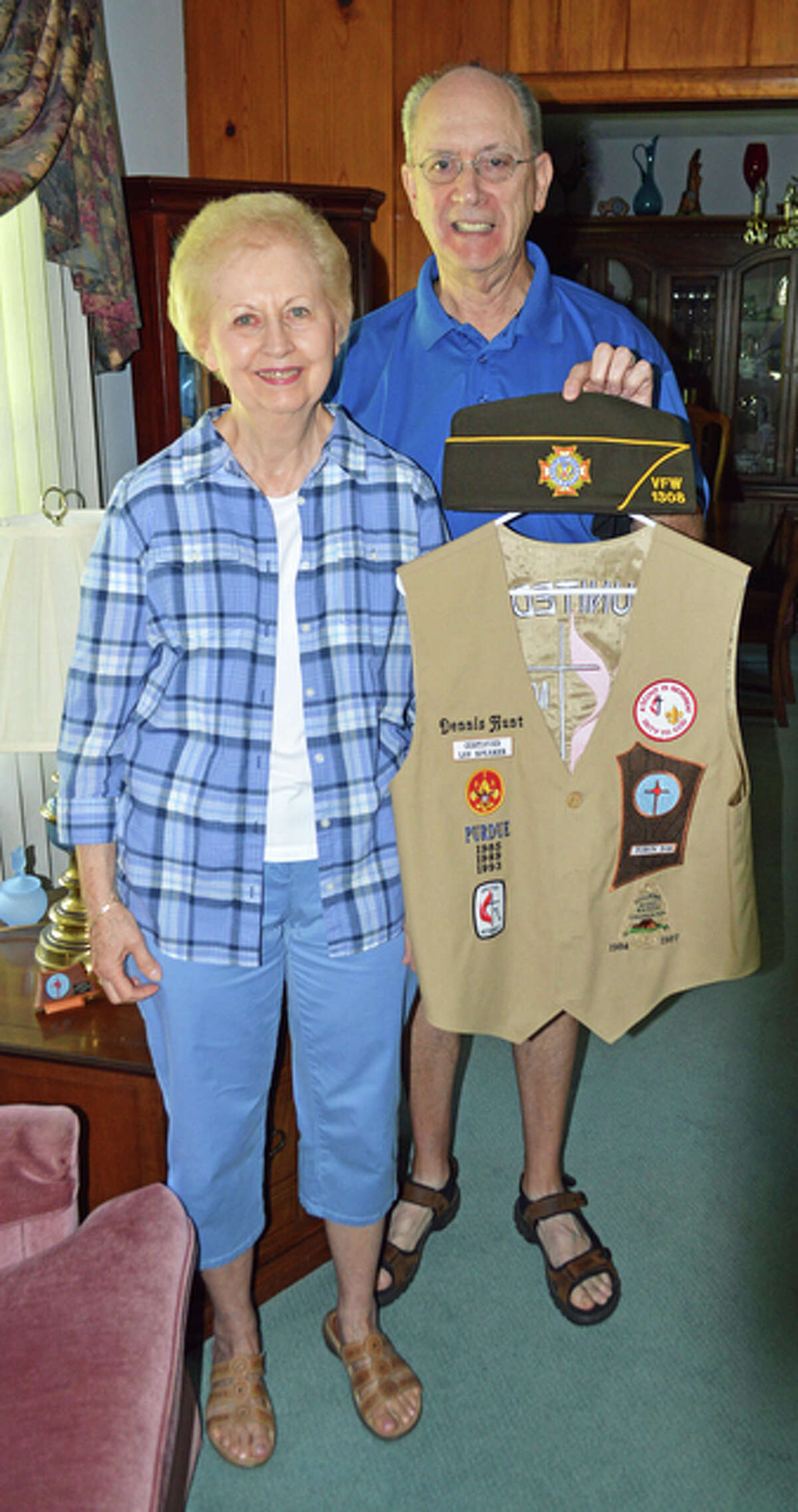 Dennis, holds his United Methodist Men vest and his VFW 1308 hat, with his wife, Sharon, in their East Alton home.