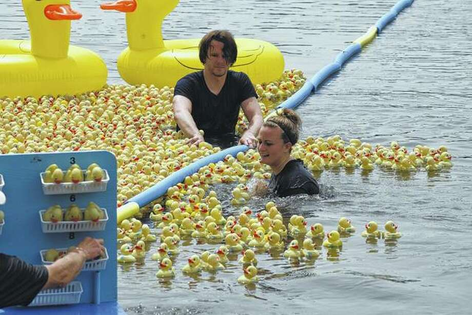 Dan Selway and Becky Griffel are outnumbered Sunday as they try to contain escaped rubber ducks during the annual Duck Race for Lifeline at Nichols Park. The event raises money to buy Lifeline units and to provide service to those unable to afford it.
