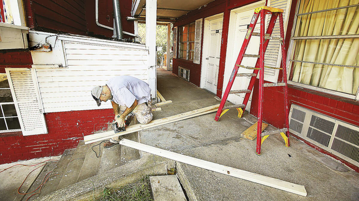 A worker cuts wood Tuesday afternoon at the Hiway House on Godfrey Road in Godfrey as he tries to build a roof over the set of stairs in front of him.