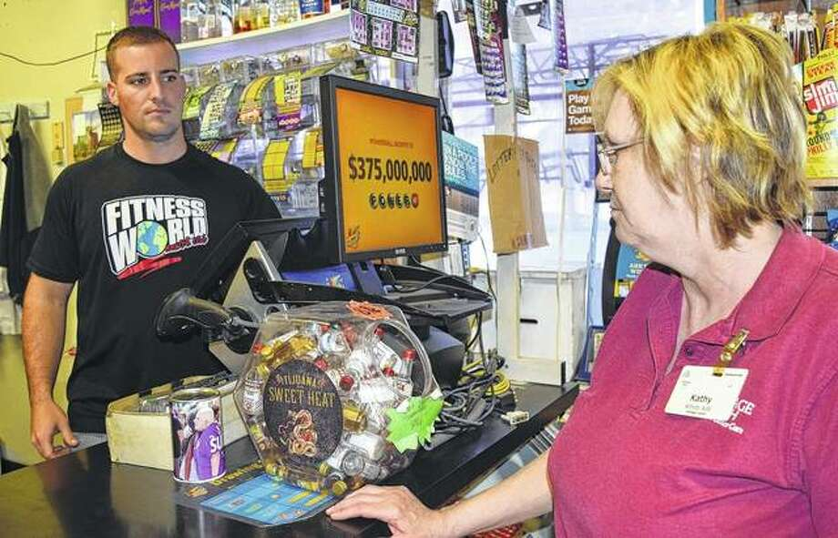 Kathy Sims of Jacksonville buys a Powerball ticket Monday at Dunlap Court Beverages from manager Brock Ridings.