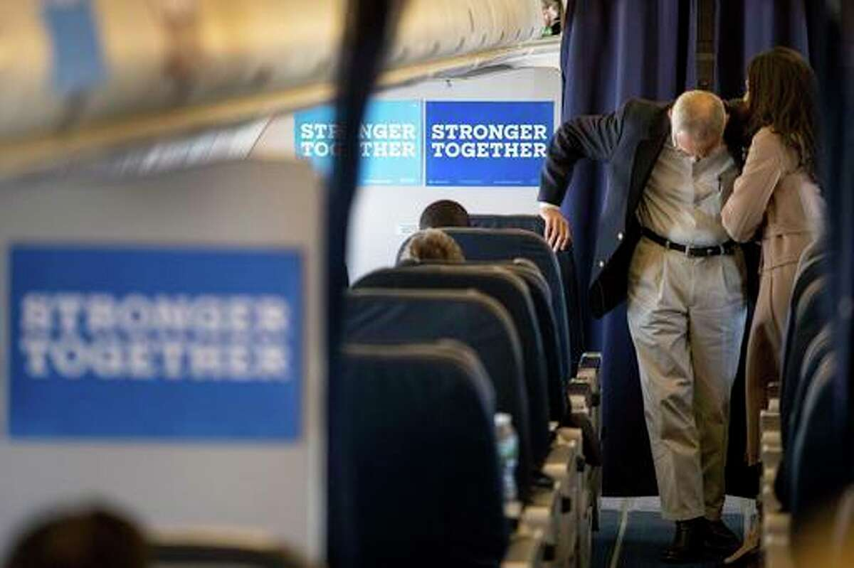 Hillary Clinton's campaign manager John Podesta, second from right, speaks with senior aide Huma Abedin, right, aboard Clinton's campaign plane while traveling to Miami, Tuesday, for a rally.