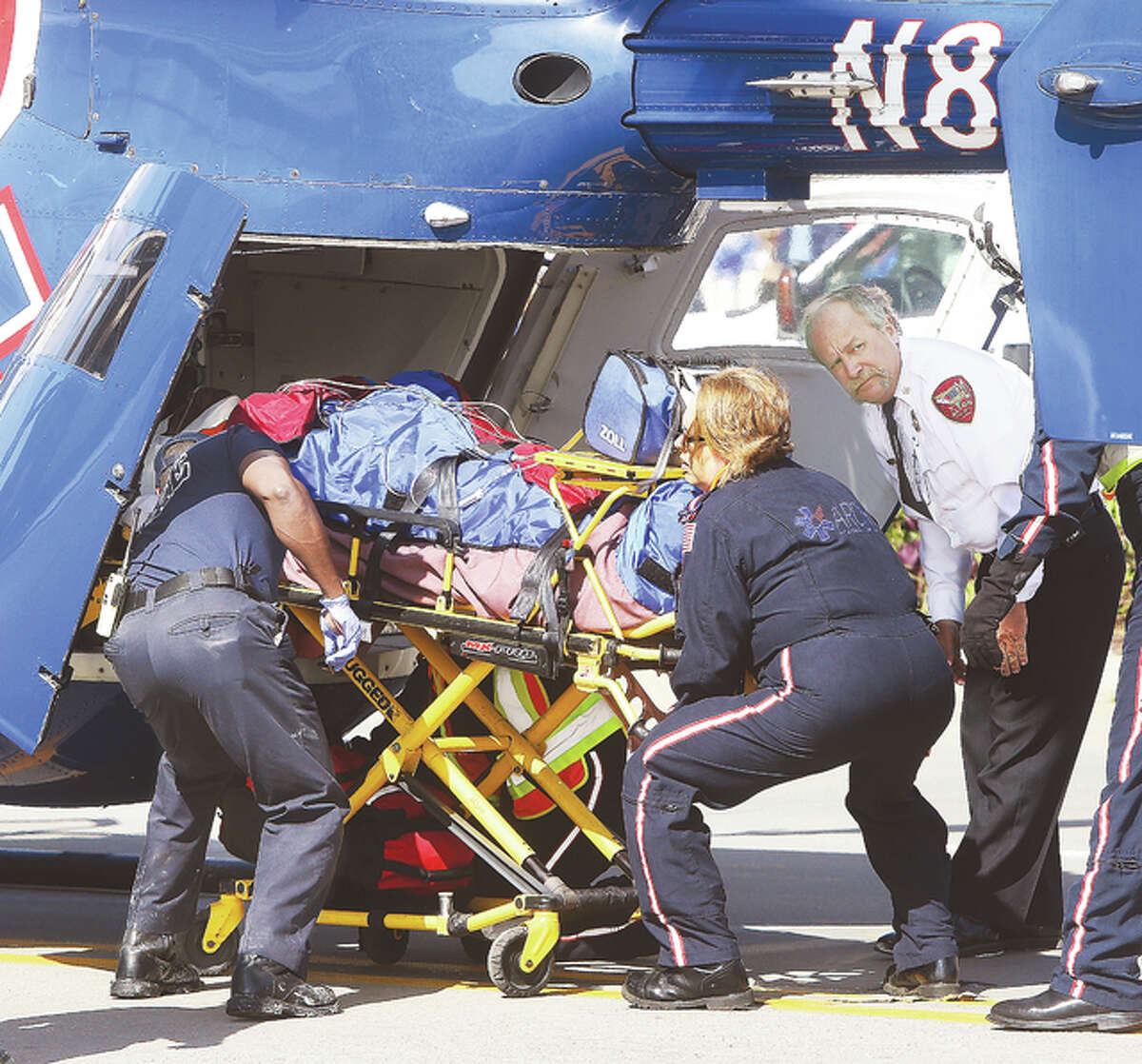 ARCH Air Medical Services Inc. flight nurses and Alton Battalion Chief Brad Sweetman, right, load the forklift driver into the helicopter for an airlift to St. Louis.