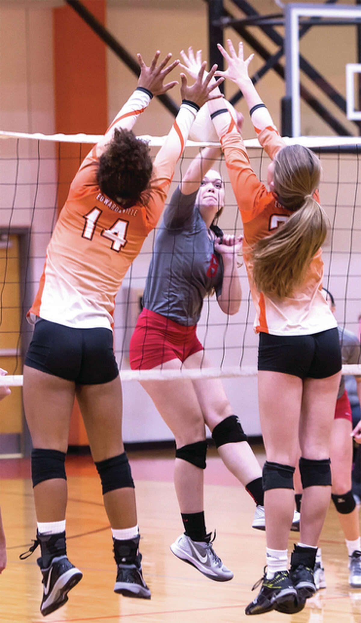 Alton's Saddi Brands (middle) hits into the block put up by Edwardsville's Maria Smith (left) and Kate Martin during SWC volleyball Thursday in Edwardsville.
