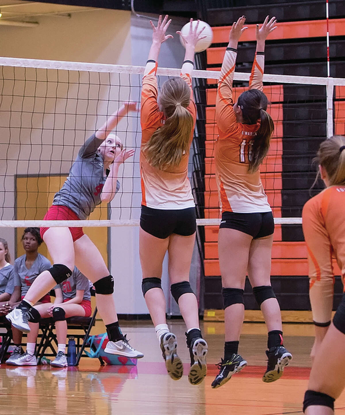 Edwardsville's Kate Martin (middle) and Corrine Timmermann (right) put up a block on the attack from Alton's Gwendolyn Hunter during the Tigers' Southwestern Conference victory Thursday night at Lucco-Jackson Gym in Edwardsville.