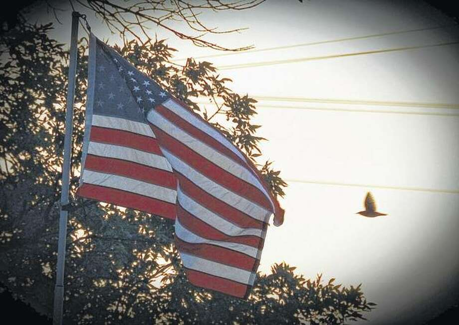 A flag flies in the wind at the elementary school in Winchester as the sun sets for the day. Photo: Elizabeth King | Reader Photo
