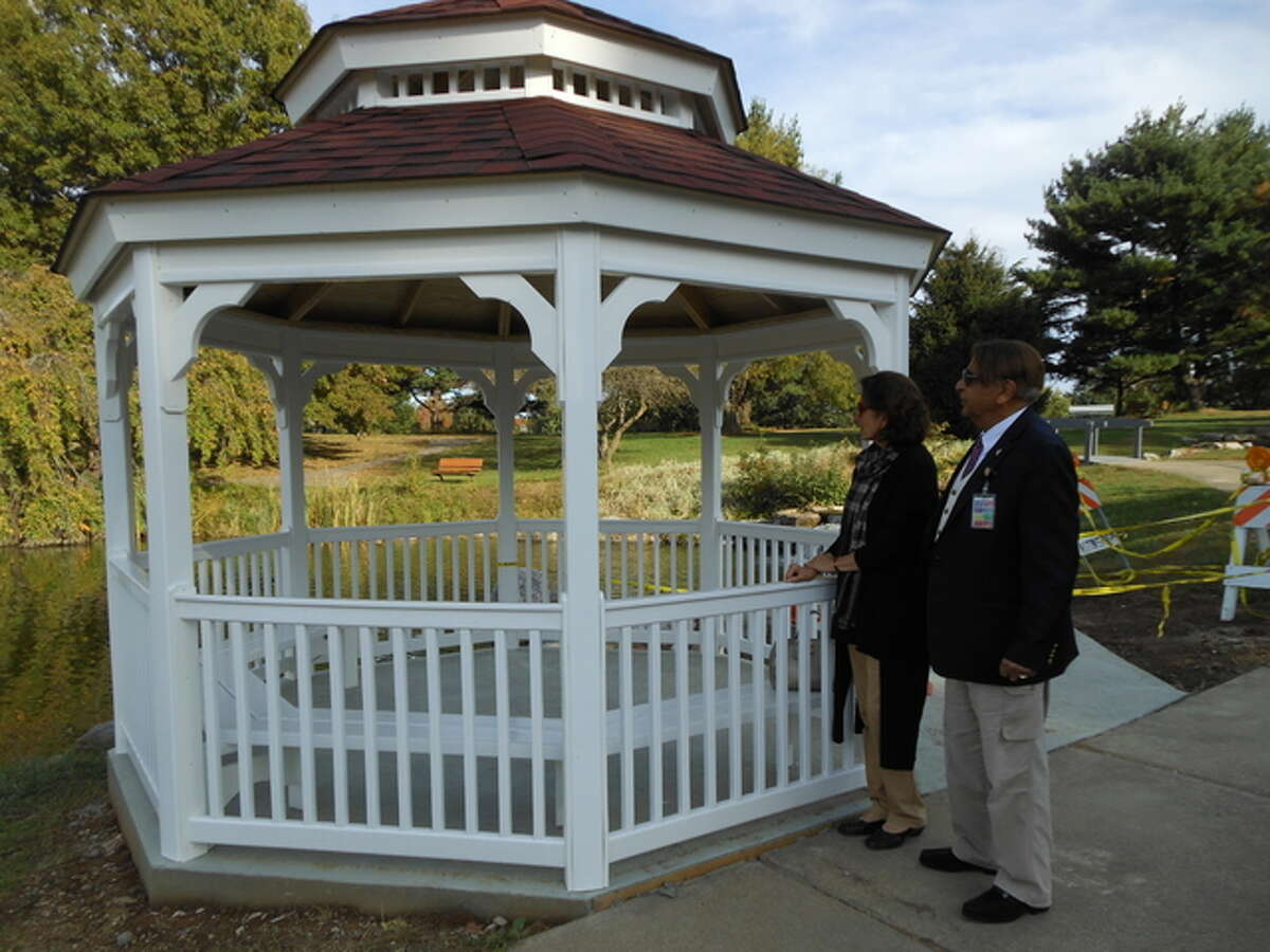 Dr. Sadiq and Talat Mohyuddin, founders of the Oriental Garden, admire the newly completed gazebo that Jun Construction workers assembled this week at the garden, in Gordon F. Moore Community Park. The $7,717 structure replaced a circa 1985 wooden gazebo the city demolished, the new one paid for with donations. The city paid for the assembly and concrete pad and walkway.