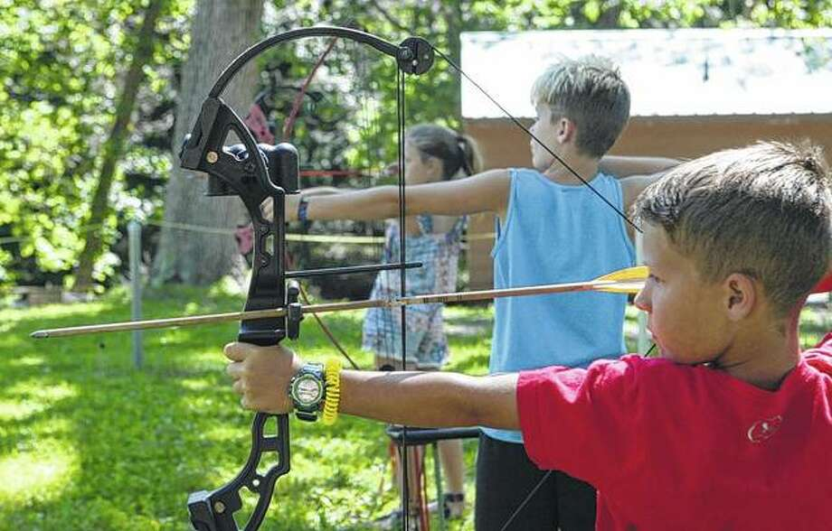 Eli Blankenship, 8, of Jacksonville (foreground), Gavin Little, 9, of Franklin and Lola Rowe, 9, of Jacksonville hone their archery skills Wednesday at Western Illinois Youth Camp's summer camp. The nine-week camp ends Aug. 11.