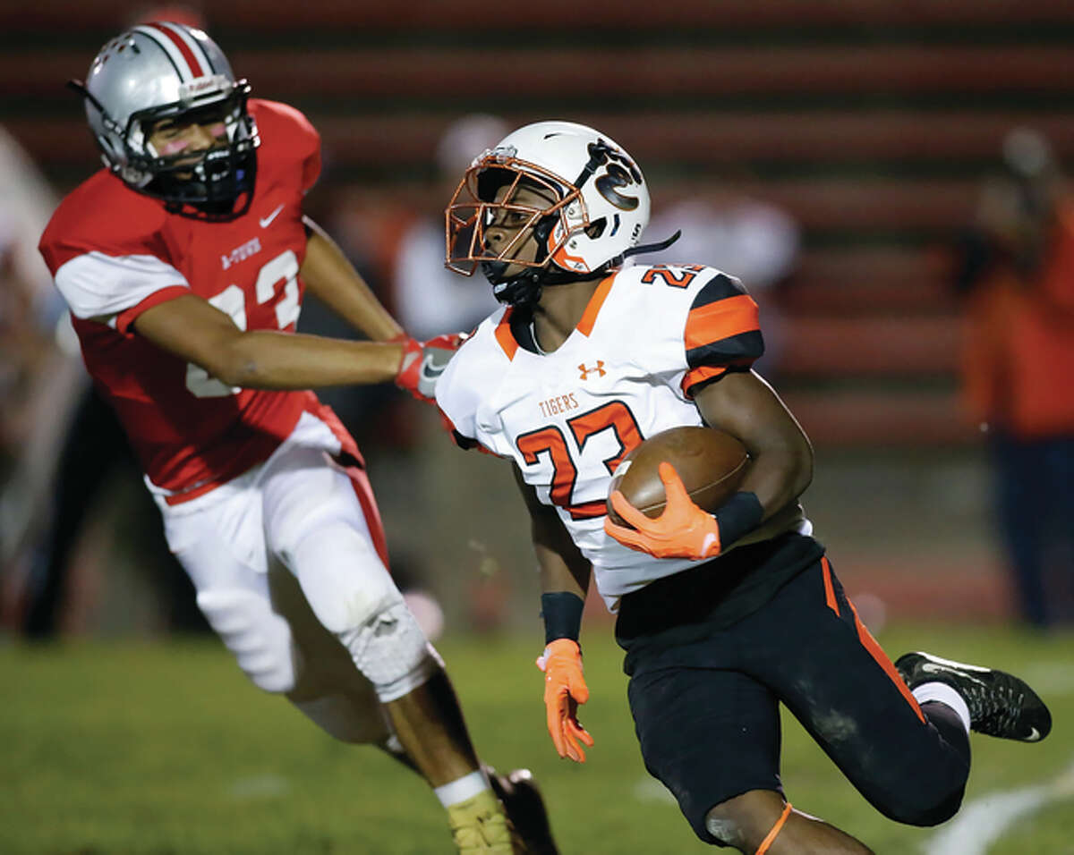 Alton's Morris Adams (left) pursues the play while Edwardsville running back Dionte Rodgers turns the corner during Southwestern Conference football action Friday night at Public School Stadium in Alton.