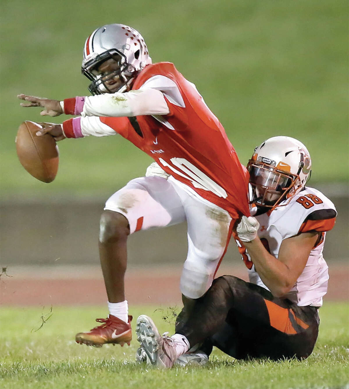 Alton quarterback Taylor Price (left) is brought down by Edwardsville's Nathan Kolesa on Friday night in Alton.