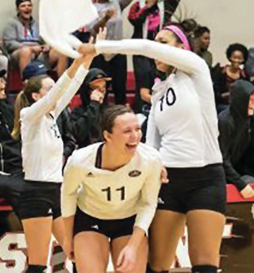 SIUE's Taylor Held (11), Madison McKinley (10) and Sami Knight celebrate a Cougars point from the bench during their five-set OVC victory over Morehead State on Friday night at the Vadalabene Center in Edwardsville. Photo: SIUE Athletics