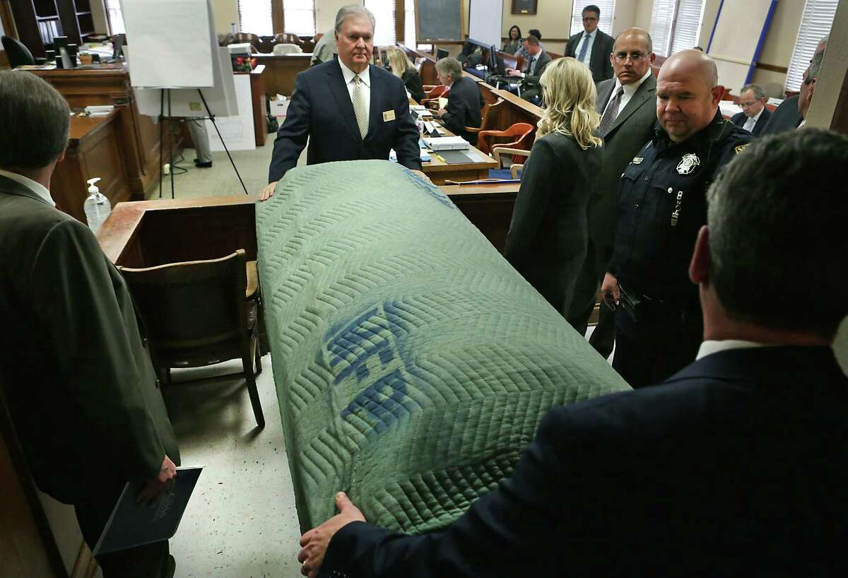 """Robert """"Dick"""" Tips (top) removes a coffin from the courtroom Wednesday during the civil case against his funeral business."""
