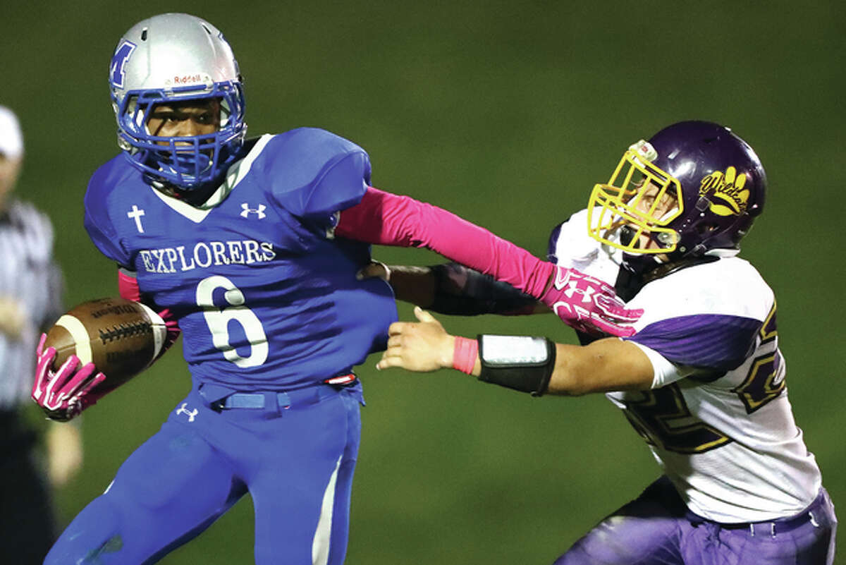 Marquette's Treven Swingler (left) eludes Mount Olive's Jonathon Darrah during Saturday night's Prairie State Conference football game at Public School Stadium. The Explorers, winners of six in a row, beat the Wildcats 45-6 to clinch at least a share of their first PSC title since winning the league back-to-back in 2012-13. The Explorers, 6-2 and 6-0 in the conference, can win the PSC outright next week at Kincaid South Fork, which is 5-3 and 5-1 in the league.