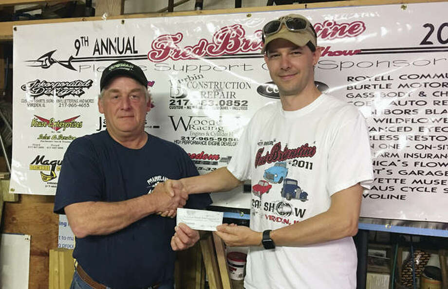 Rob Miller (right), a member of the organizing committee of the Fred Britenstine Memorial Car Show, presents a check representing proceeds from the 2016 event to Brian Williamson (left) of Prairieland Ambulance to help the ambulance service upgrade to include advanced life support. The event, once known as the Virden Car Show, honors the memories and passions of Fred Britenstine, a long-time Virden resident, Vietnam veteran, volunteer firefighter and custom car/hot rod builder and owner. The 10th annual show will be Saturday with registration from 8 a.m. to noon on Route 66 in Virden. For more information, email virdencarshow@gmail.com. Photo: Photo Provided