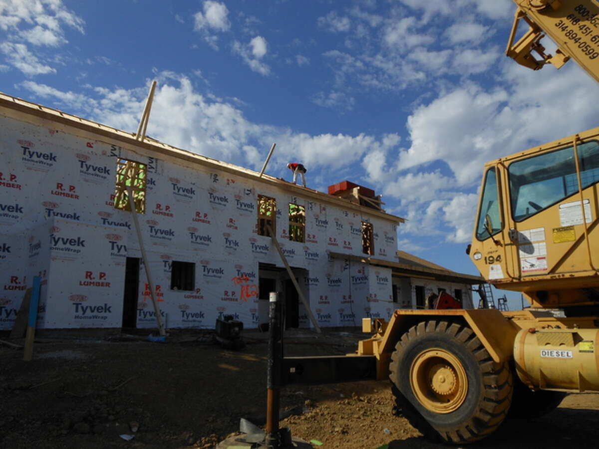 An employee of general contractor Morrissey Construction Co., of Godfrey, works on the roof of the first of 13 buildings going up at the Madison County Housing Authority's future, Woodland Park apartment complex in Collinsville.