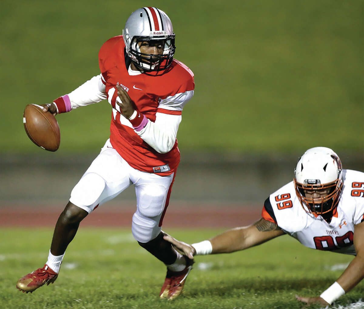 Alton quarterback Taylor Price (left) scrambles to get away from diving Edwardsville defensive end AJ Epenesa during Southwestern Conference football action Friday night at Public School Stadium in Alton.