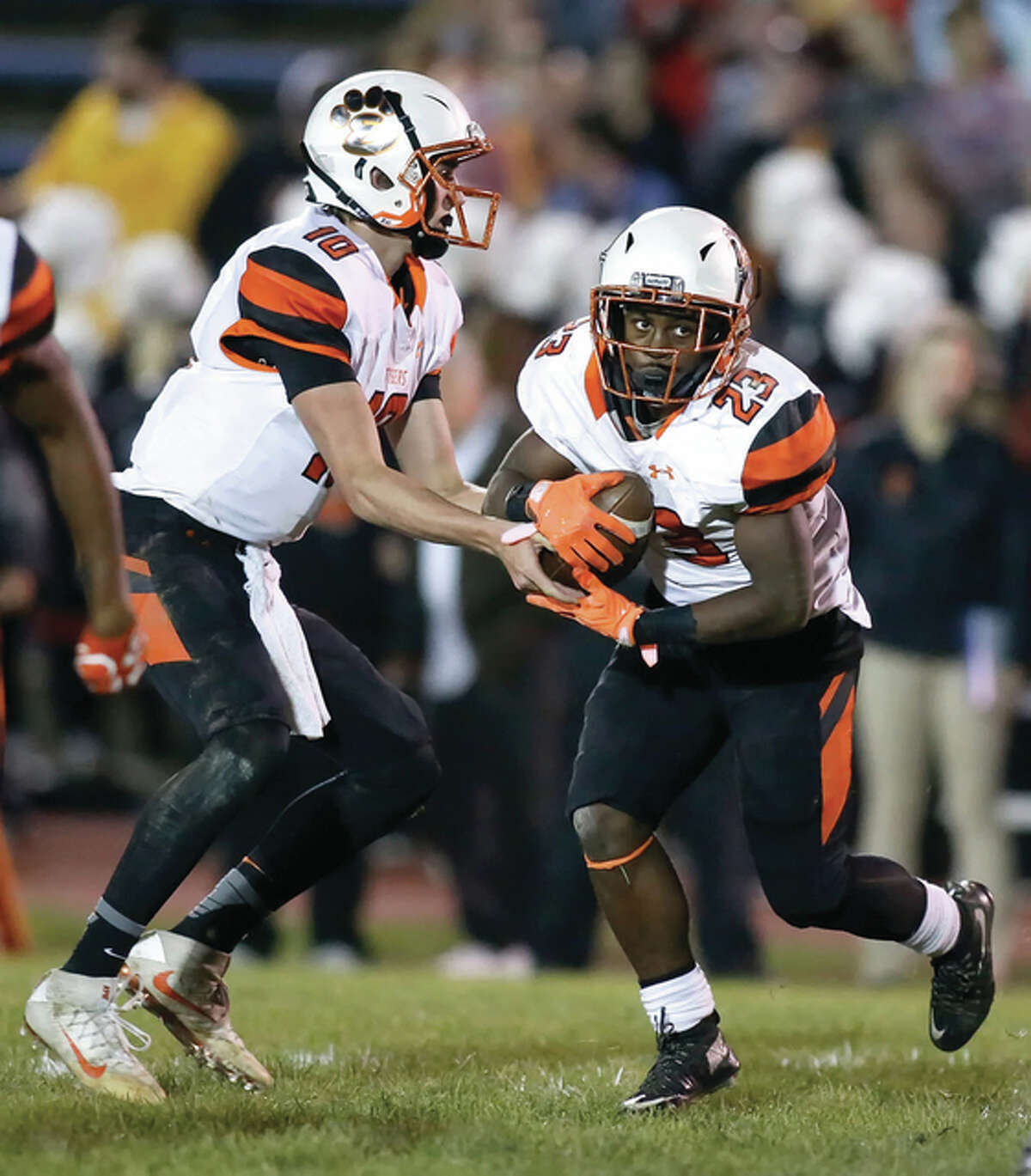 Edwardsville QB Brenden Dickmann (left) hands off to running back Dionte Rodgers on Friday night in Alton. Rodgers, a sophomore, finished with 211 rushing yards and three touchdowns from 16 carries.