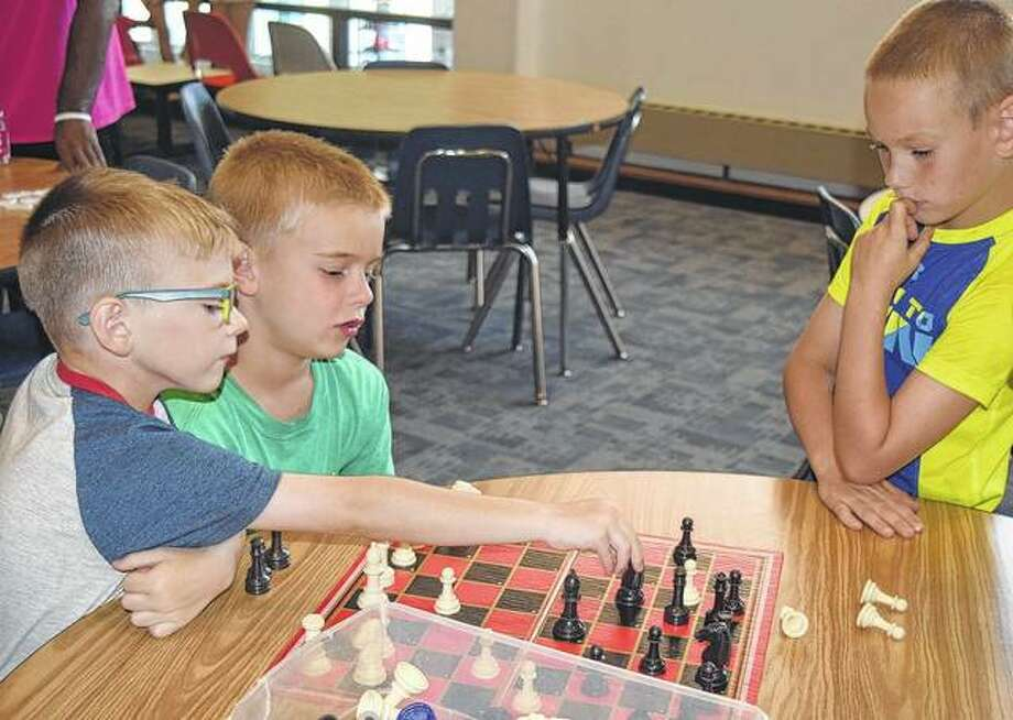 Kole Jennings (from left), 6, plays chess Monday with Rylin Rees, 7, and Jace Raye, 8, at Bob Freesen YMCA to escape the 90-degree heat. Photo: Samantha McDaniel-Ogletree | Journal-Courier