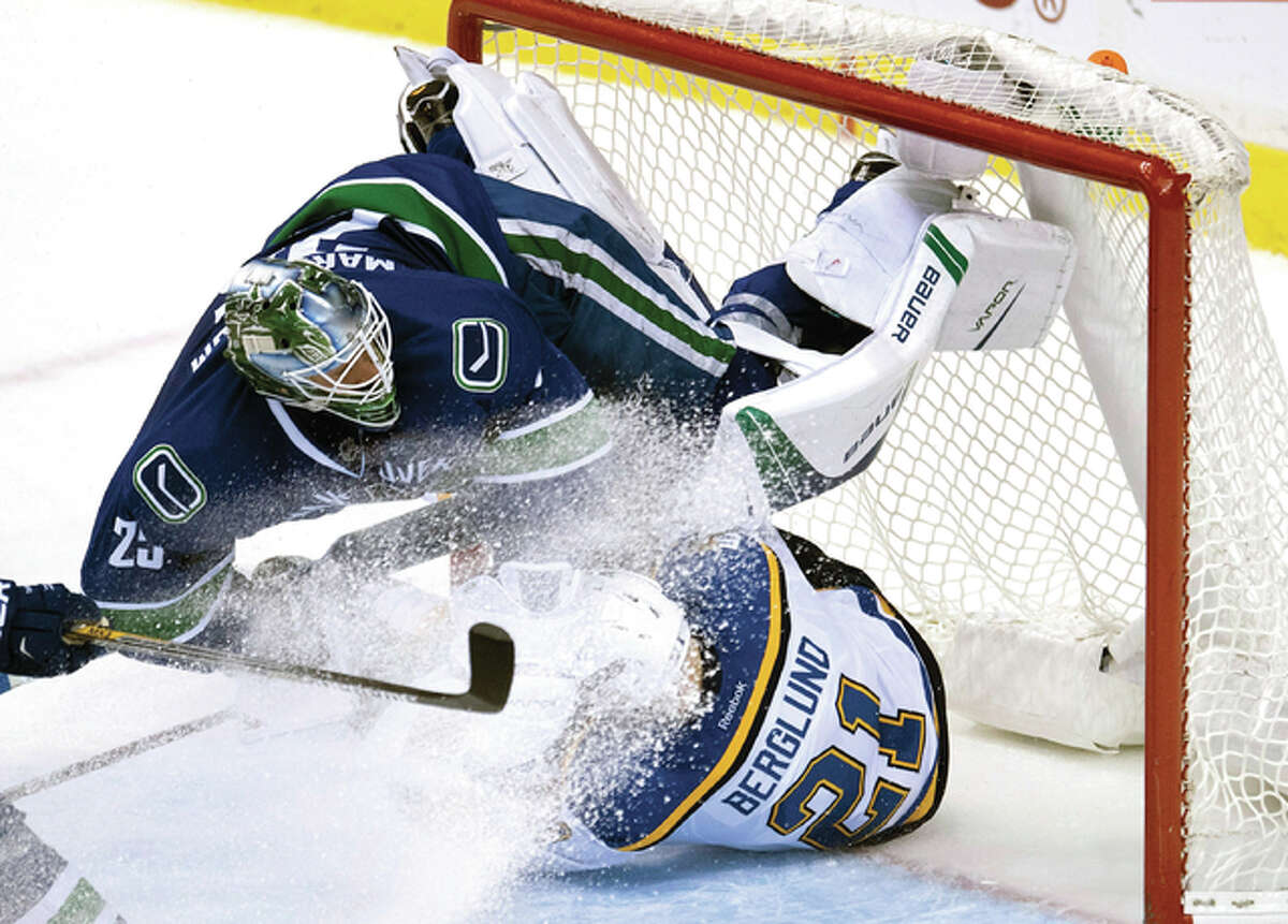 Vancouver Canucks goalie Jacob Markstrom (25) gets taken out by Blues center Patrik Berglund (21) in the third period Tuesday night in Vancouver, British Columbia.