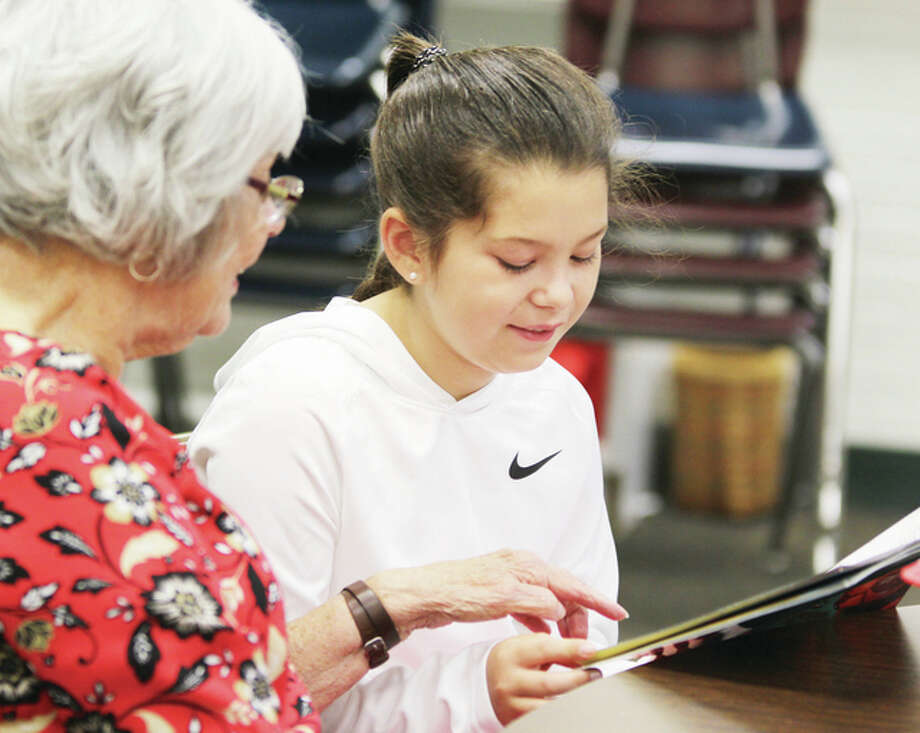 Fourth-grader Sahara Ward reads to volunteer Ruby Bryan as part of the Reach Out and Read program at Meadowbrook Intermediate School Tuesday. The school recently started a program based on the successful ROAR program in the Alton School District.