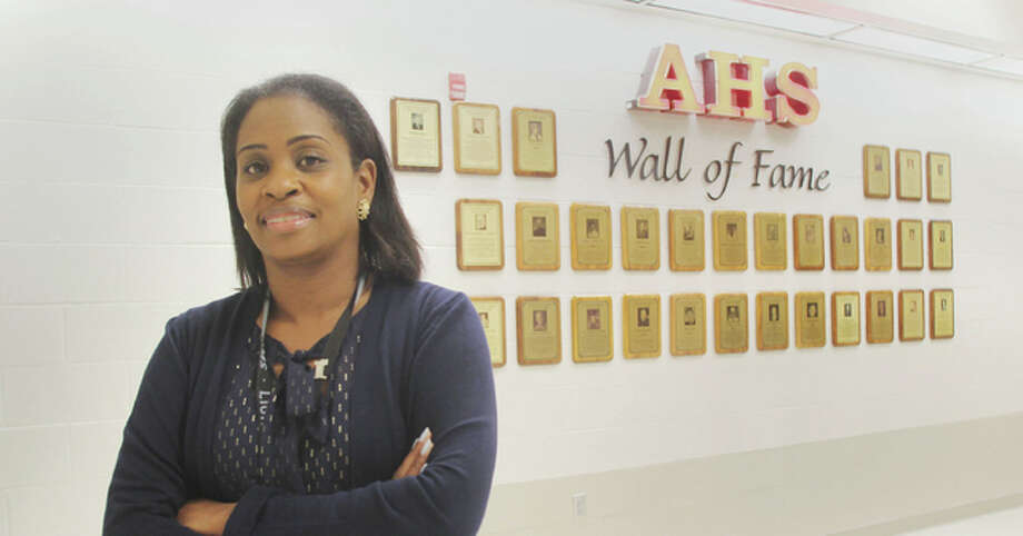 "Alton High School Assistant Principal Amy Golley stands in front of the school's ""Wall of Fame"" Wednesday morning. The school district is accepting new nominations for the wall through Nov. 30."