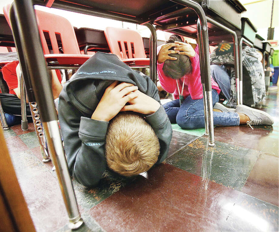 Students in the sixth grade classroom of Alton Middle School math teacher Michele Perretti duck and cover in place Thursday as they participate in the Great Central U.S. ShakeOut earthquake drill.