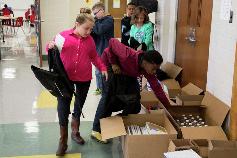 Fifth graders at North Elementary School in Alton prepare backpacks to send to their counterparts in Louisiana.
