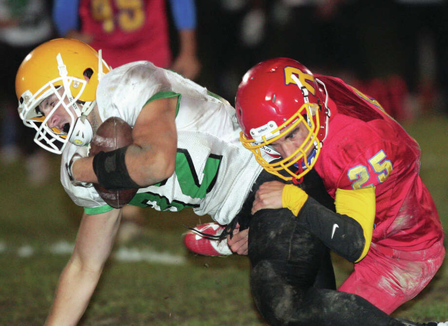Southwestern's Lucas Kaiser is pulled down by Roxana's Ethan Arnold after a 21-yard pass play for a first down as the Piasa Birds in the second quarter Friday night in Roxana. Photo: James B. Ritter | For The Telegraph