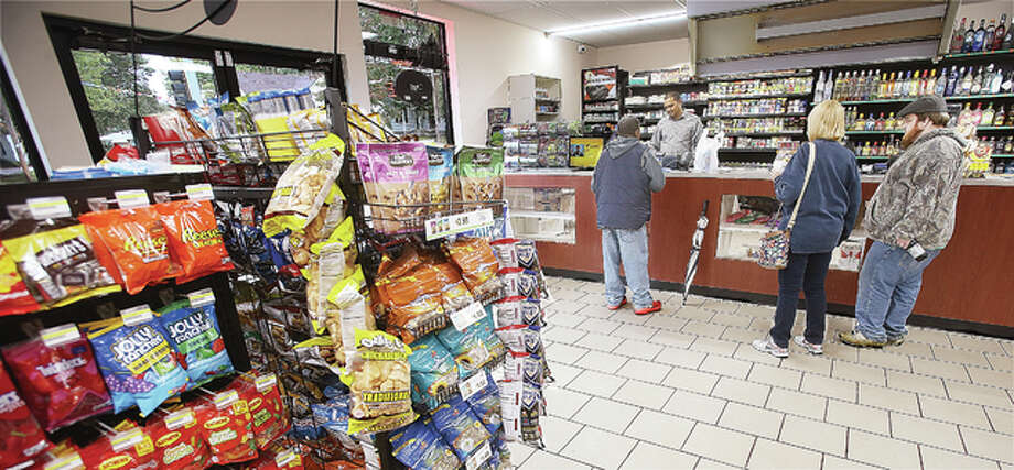 Customers line up to make purchases this week at the now open Milton Food and Liquor Store on Milton road. The new store sits in the same spot as the former Milk Store, which was razed to build the new building. The new establishment has considerably more parking space than the old Milk Store.