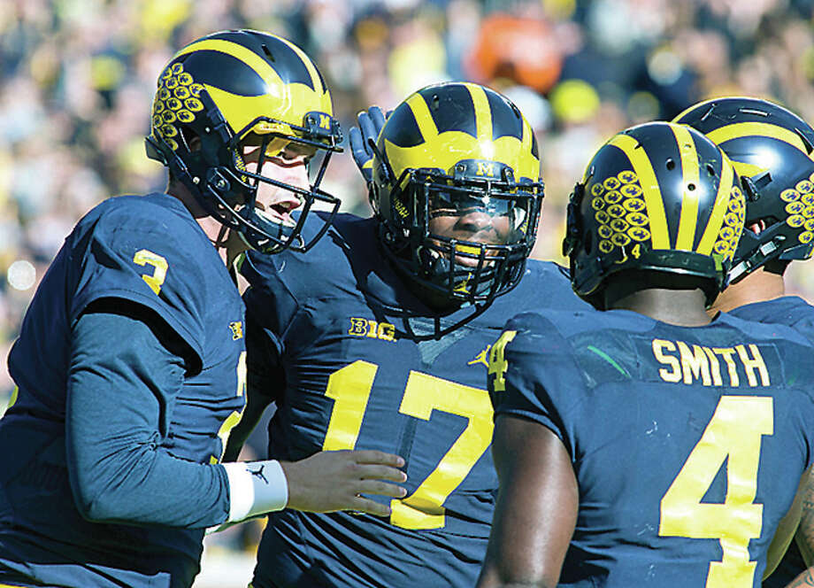 Michigan quarterback Wilton Speight, left, celebrates a touchdown against Illinois with tight end Tyrone Wheatley (17) and running back De'Veon Smith (4) in the first quarter Saturday in Ann Arbor, Michigan Photo: AP
