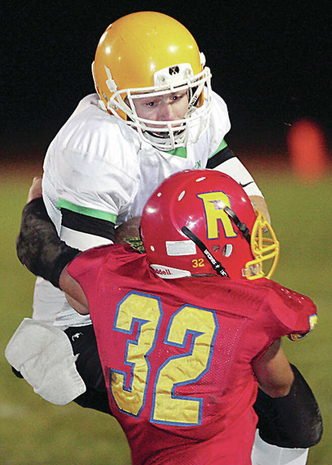 Southwestern quarterback Caleb Robinson is pulled down by Roxana's Wyatt Kirkpatrick as he scrambles for yardage Friday night in Roxana.