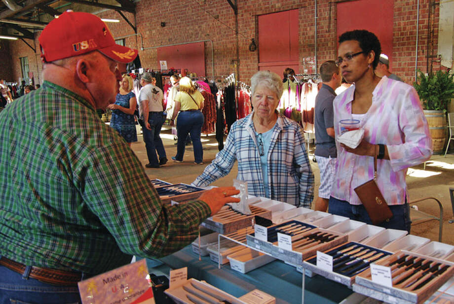 Kenny Mitchell, left, and Barbara Mitchell, center, of Jerseyville, discuss items they have for sale with Phyllis Williamson, of St. Charles, Missouri, during the final weekend of the Grafton Riverside Flea Market's season on Sunday. Photo: David Blanchette|For The Telegraph