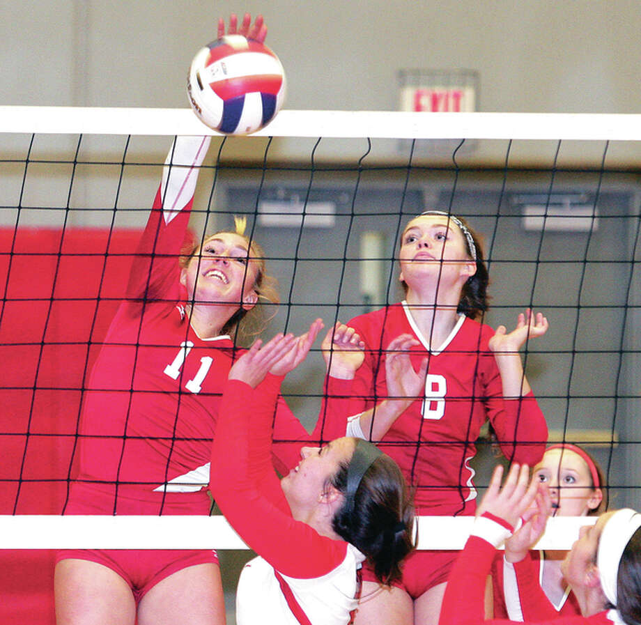 Alton senior Annie Evans, left, records a kill Monday night against Chatham Glenwood the Alton Class 4A Regional at Alton High in Godfrey. At right is Alton's Saddie Brands. Photo: James B. Ritter | For The Telegraph