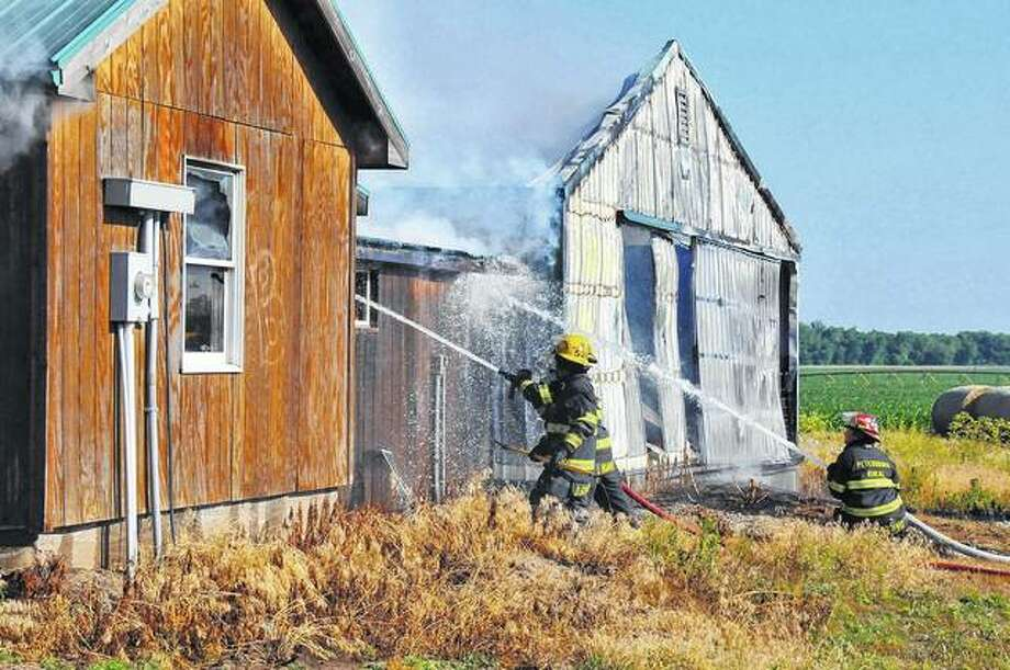 Petersburg Rural Fire Department firefighters extinguish flames after being called to a fire Wednesday at a barn on Oakford-Chandlerville Road near the Menard and Cass counties line. Photo: Robert Daniel | For The Journal-Courier