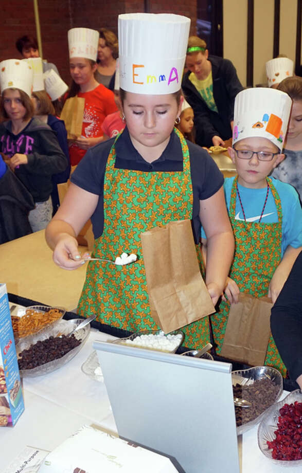 "Emma Burney and Kyle Foss of Bethalto work on a recipe during ""Kids in the Kitchen"" at Alton Memorial Hospital earlier this year."
